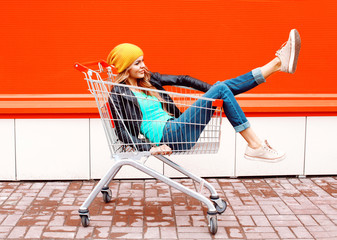 Fashion woman in trolley cart wearing black jacket hat over colo