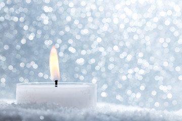 Chistmas candle glowing on glitter background.