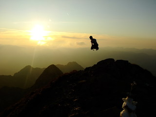 Man jumping up on the Top of the Nebelhorn Mountains in Germany Alps
