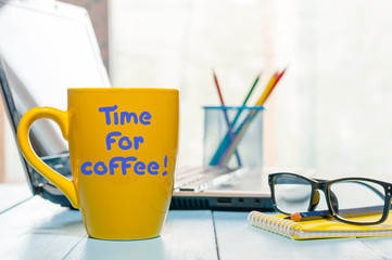 Time for coffee written on yellow cup at business office workplace background. Fun calligraphy typography greeting and invitation card. with empty space