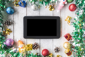 Top view of Tablet with Christmas decoration on white wooden table
