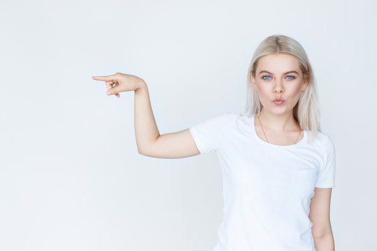 Beauty young woman pointing away over white background