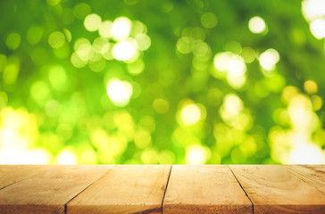 Empty of wood table top on blur of fresh green bokeh background