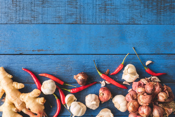 Top view of  Red onion with Garlic, Red hot chilli peppers and Garlic on blue wooden table background.