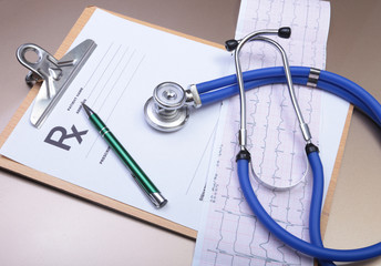 Stethoscope head and silver pen lying on cardiogram  clipboard pad. Cardio therapeutist assistance, physician make cardiac physical, pulse beat measure document, arrhythmia idea, pacemaker concept