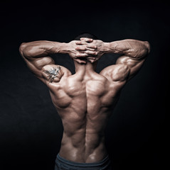 strong athletic mans back on dark background
