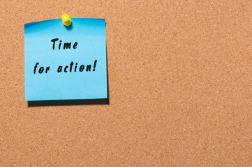 Time for Action written on blue sticker pinned to cork notice board. With empty space