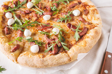 Thick-crust pizza with hunting sausages, mozzarella cheese on a white wooden background