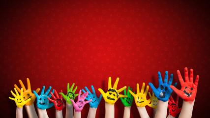 viele angemalte Kinderhände mit Smileys vor weihnachtlichem Hintergrund