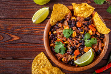 Chili con carne in bowl with tortilla chips.
