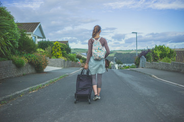 Woman with luggage in suburbia
