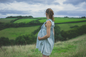 Young pregnant woman standing in countryside