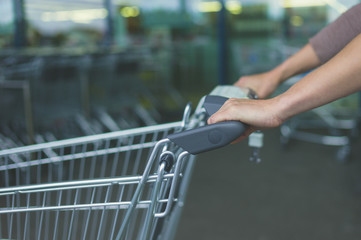 Hands of woman pushing shopping trolley
