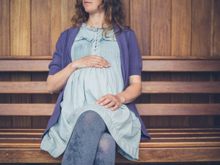 Pregnant woman sitting on bench in shelter