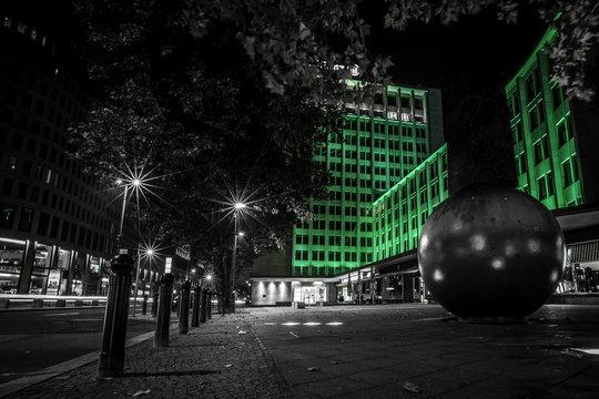 Pendelobelisk vor grün beleuchteter Hauswand in Berlin