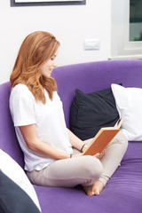 Smiling woman relaxing with a book on a purple sofa