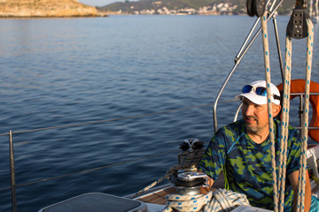 Mature man on sailing yacht boat in the sea.