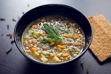 lentil soup in a black bowl on dark wooden table