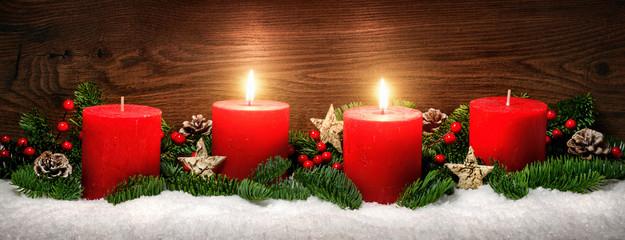 Advent Dekoration mit zwei Kerzenflammen, Schnee, Tannenzweigen und Holz Hintergrund