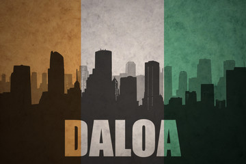 abstract silhouette of the city with text Daloa at the vintage ivorian flag