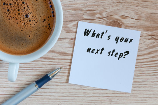 Hand writing the text Whats Your Next Step. Morning coffee at wooden table background