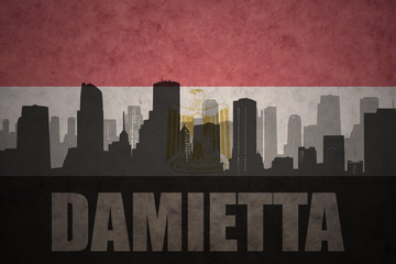 abstract silhouette of the city with text Damietta at the vintage egyptian flag