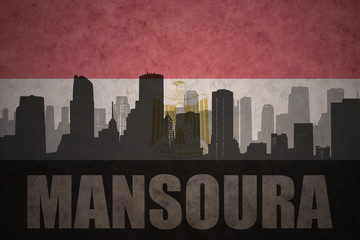abstract silhouette of the city with text Mansoura at the vintage egyptian flag