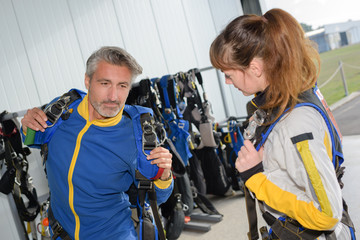 Man in jumpsuit putting on harness
