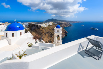 Blue dome of church in Imerovigli village and view of blue sea with caldera on Santorini island, Greece