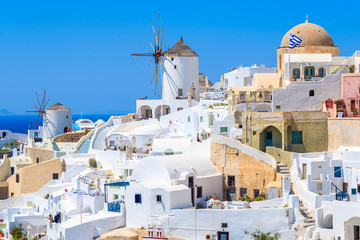 White houses and traditional windmill in Oia village on Santorini island, Greece