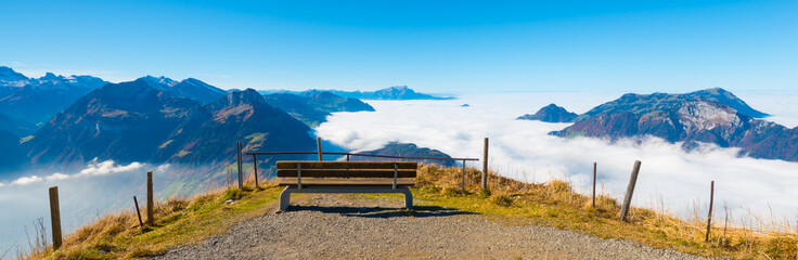 Morschach Stoos. Aerial view. Peak. Bench to rest on the edge. Below clouds and a lake.