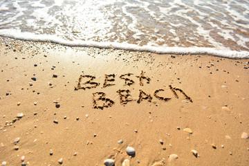 the inscription on the sand near the sea on a sunny day