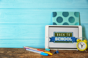 Colourful stationery and tablet with BACK TO SCHOOL phrase on turquoise wooden background