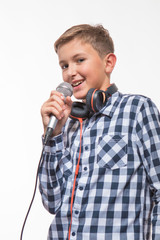 Emotional singer blonde boy in a plaid shirt with a microphone and headphones on a white background