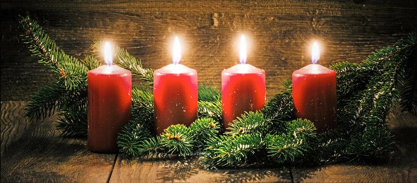 Vierter Advent: vier leuchtende Kerzen vor einem Holzhintergund