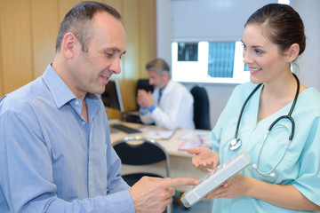 Nurse showing pill box to patient