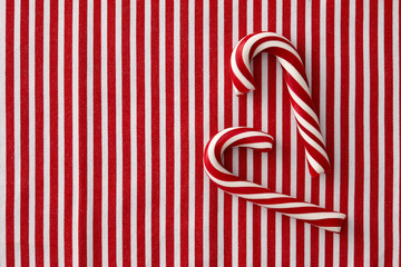 Striped peppermint candy canes on a striped background