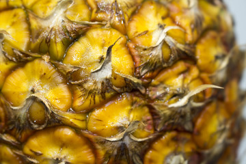 Pineapple surface close-up photo. Natural fruit skin wallpaper or background.