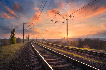 Railroad against beautiful sky at sunset. Industrial landscape with railway station, colorful blue sky with red  clouds, trees and green grass, yellow sunlight. Railway junction. Heavy industry Wall mural