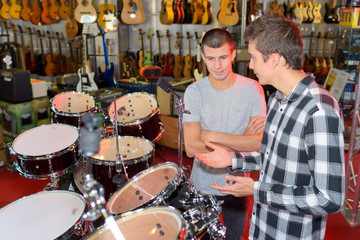 Two young men looking at drum stets in a store