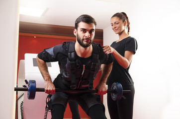 Handsome man working out with female trainer supervision, EMS. Muscle stimulation