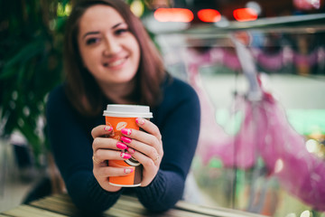 Smiling Girl holding a Cup of coffee. Manicure in pink colors