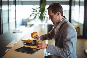 Businessman having breakfast in cafeteria