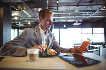 Businessman having breakfast in cafeteria