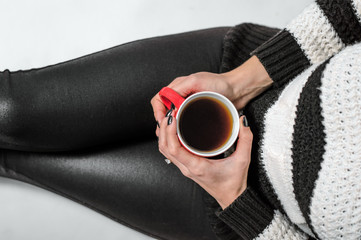 A girl holding a red cup of tea in her arms