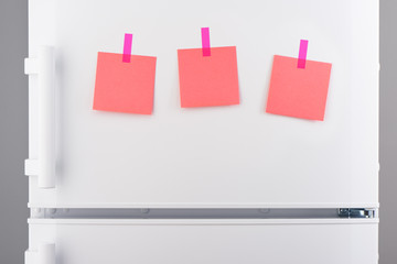Pink paper notes attached with stickers on white refrigerator