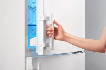 Female hand opening white refrigerator door on gray