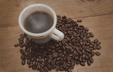 Steaming Cup of Hot Coffee Surrounded by Beans