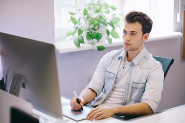 Young worker sitting in an office at the computer. Freelancer in a blue shirt. The designer sits in front of window in the workplace.