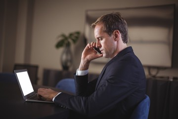 Businessman talking on the phone while using laptop